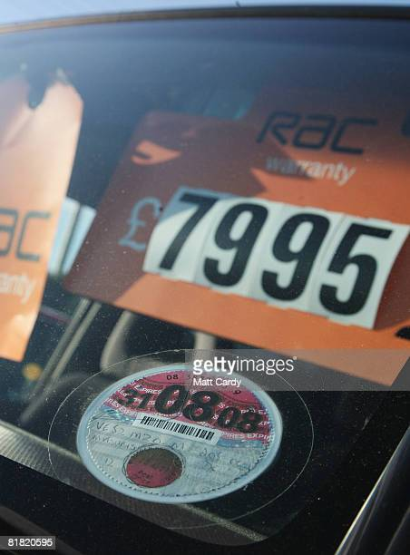 A tax disc is displayed on a second hand car for sale is parked on a used car lot on July 4 2008 in Bristol England The value of second hand cars are...