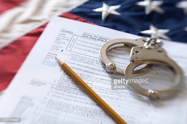 US Tax Form and Hancuffs over American Flag Selective Focus