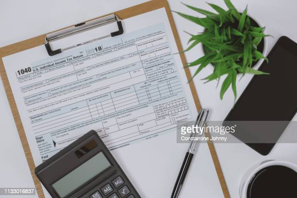 tax form on clipboard, calculator and mobile phone on work desk - 1040 tax form stock photos and pictures