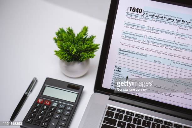 tax form on laptop screen on work desk with pen and calculator - 1040 tax form - fotografias e filmes do acervo
