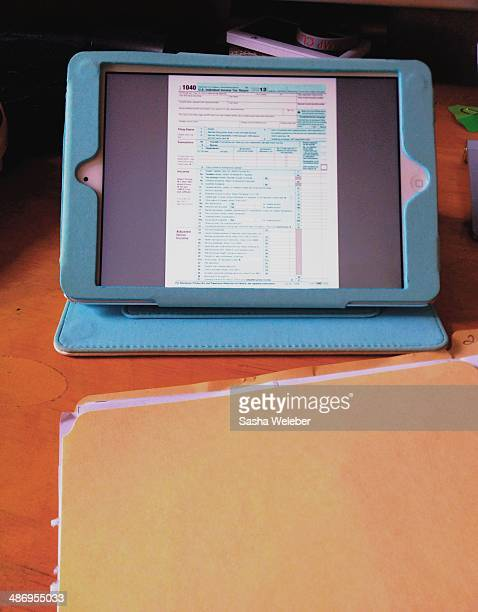 Tax Form on tablet with tax information folder on table