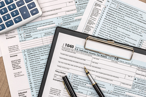 1040 tax form on wooden table with pen and calculator 1001566296