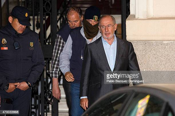 Tax office agents and police lead former IMF chief Rodrigo Rato into a car after raiding his private office in fraud probe on April 16 2015 in Madrid...