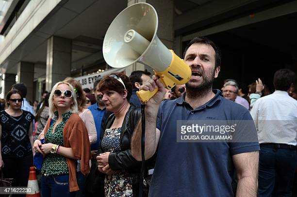 A tax office worker uses a loudspeaker during a protest outside the Finance Ministry in Athens on April 30 2015 Moody's downgraded Greece's debt...