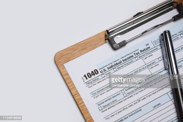 tax on wooden blocks on top of work desk space - 1040 tax form stock photos and pictures