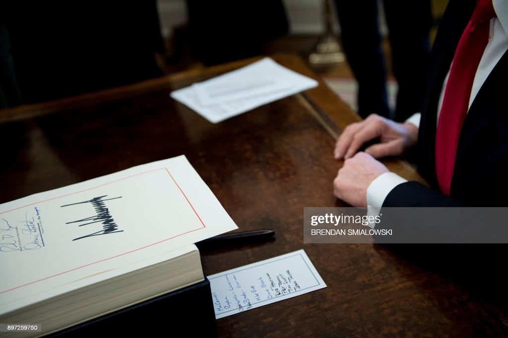 A tax reform bill is seen after being signed by US President Donald Trump in the Oval Office of the White House December 22, 2017 in Washington, DC. / AFP PHOTO / Brendan Smialowski