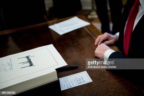 A tax reform bill is seen after being signed by US President Donald Trump in the Oval Office of the White House December 22 2017 in Washington DC /...