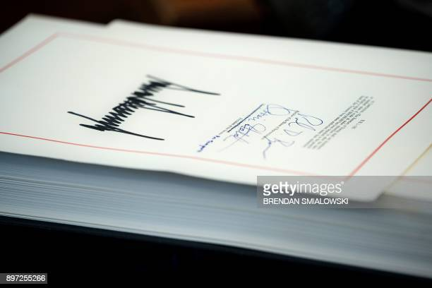 A tax reform bill signed by US President Donald Trump is seen in the Oval Office of the White House December 22 2017 in Washington DC / AFP PHOTO /...