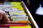 Tax refund ideas filing taxes woman's hand in filing cabinet