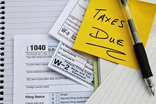 Tax return forms and wage statements with note Taxes Due. 1082680096