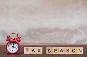 Tax season with wooden alphabet blocks and Red alarm clock, on Table dark plank wooden background with copy space