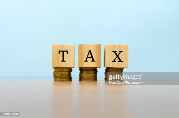 tax text written on wooden block with stacked coins - tax stock photos and pictures