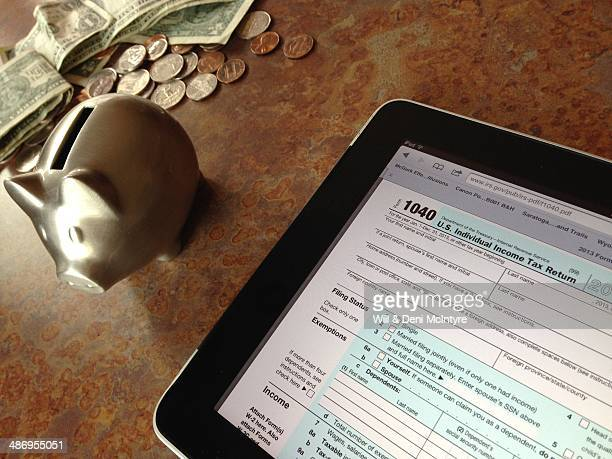 US tax time A standard 1040 form with some analog cash from a piggy bank