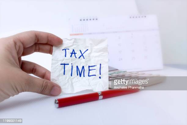 tax time concept; hand is holding tax time written on the white paper note with a red pen and calendar. - ora legale foto e immagini stock