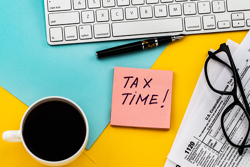 Tax Time  written on  paper note with tax form, and cup of coffee 1127781006