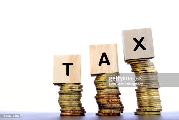 Tax Word on Wood Block on Top of Coins Stack