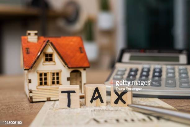 tax word on wooden block with calculator and tax form - government stock pictures, royalty-free photos & images