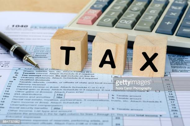 tax word on wooden block with calculator and tax form - 1040 tax form stock photos and pictures