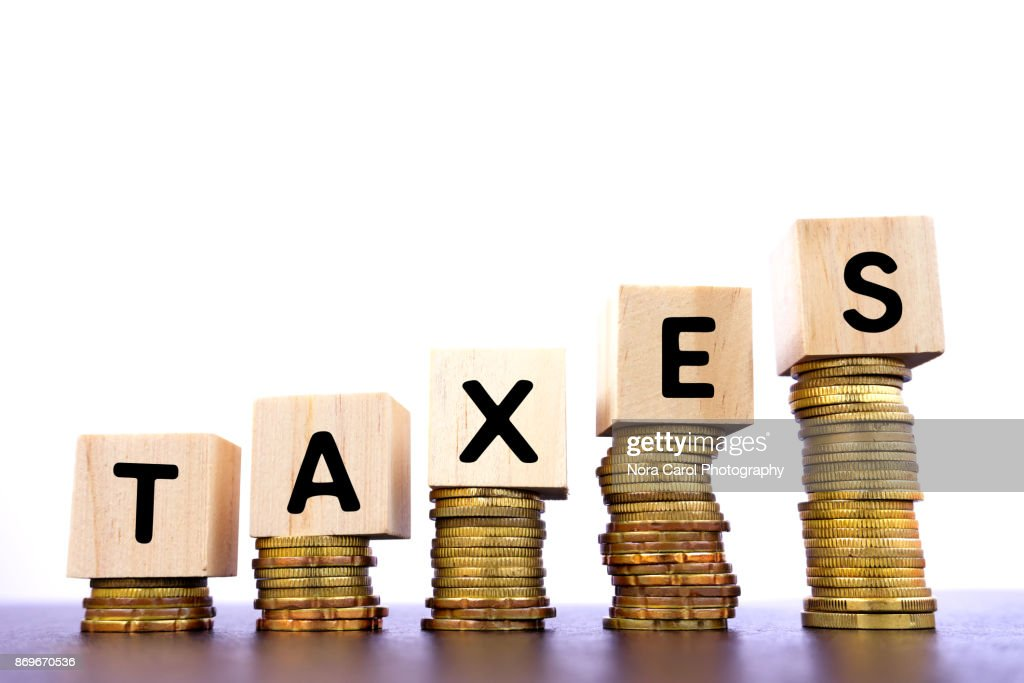 Taxes Word on Wood Block on Top of Coins Stack : Stock Photo