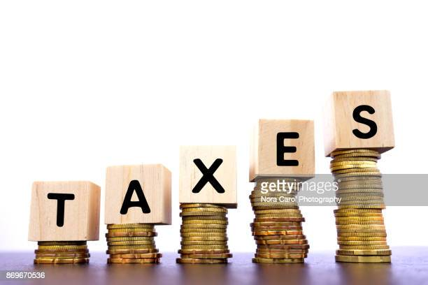 Taxes Word on Wood Block on Top of Coins Stack