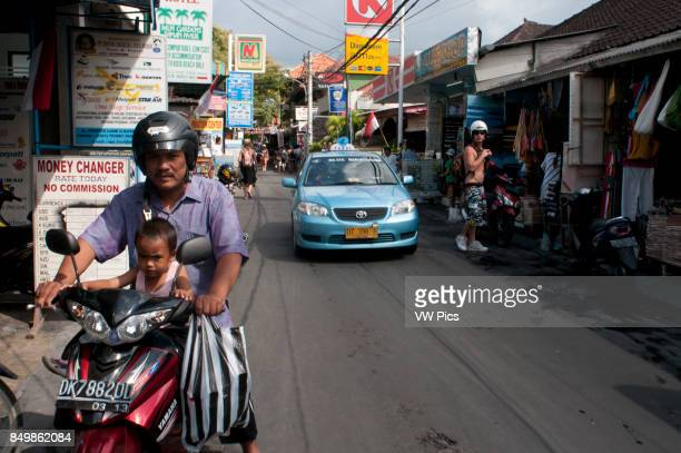 Taxi and motorbike in the Streets of Kuta Indonesia Bali touristic streets of Kuta Bali