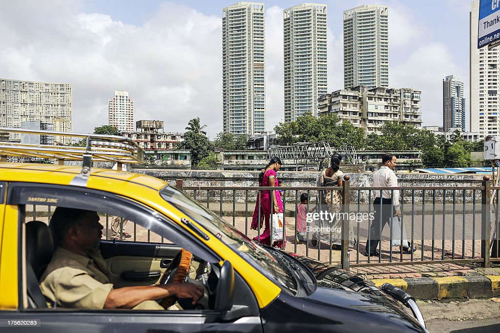A taxi and pedestrians pass in front of new and old residential buildings in the Chembur area of Mumbai, India, on Sunday, Aug. 4, 2013. India's purchasing managers index (PMI) for services figures for July are scheduled for release on Aug. 5. Photographer: Dhiraj Singh/Bloomberg via Getty Images