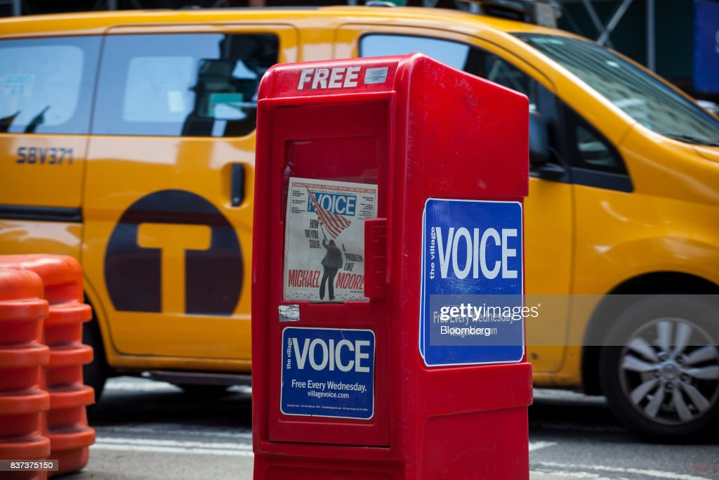 A taxi cab drives past a distribution box for The Village Voice in the East Village neighborhood of New York, U.S., on Tuesday, Aug. 22, 2017. Peter Barbey, owner of The Village Voice since 2015, has decided to no longer produce a print edition of the alt-weekly publication. The company's announcement, made Tuesday afternoon, came as a surprise, a shock and a disappointment to the larger media industry on Twitter. Photographer: Michael Nagle/Bloomberg via Getty Images