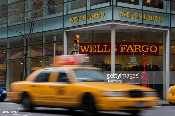 A taxi cab drives past a Wells Fargo Co bank branch in New York US on Monday April 7 2014 Wells Fargo Co is expected to release earnings figures on...