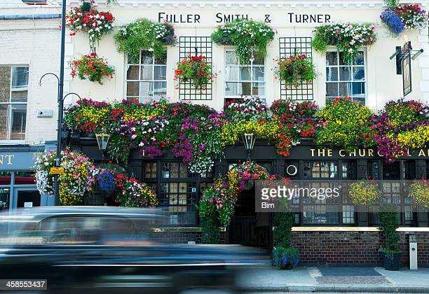 Taxi Cab Driving Past Traditional London Pub Decorated with Flowers