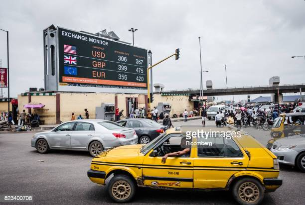A taxi cab passes a giant advertising screen showing US dollar British pound and euro foreign currency exchange rates on a busy city road in Lagos...