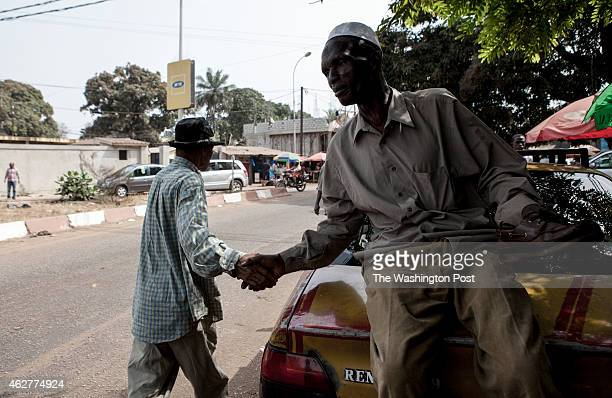 Taxi driver Abdulraman Balde greets his friend on the street on Conakry Guinea on Wednesday January 21 2015