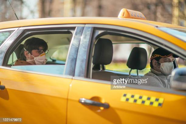 taxi driver and his passenger are wearing protective masks during air pollution or illness epidemic - driving mask stock pictures, royalty-free photos & images