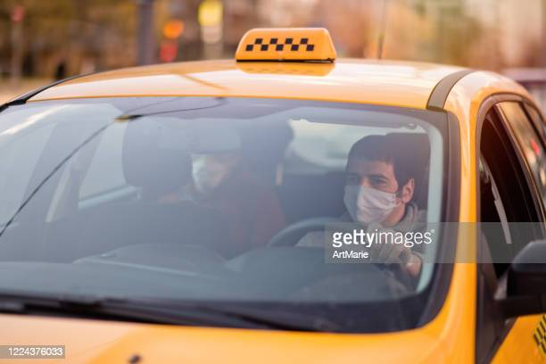 taxi driver and his passenger are wearing protective masks during air pollution or illness epidemic - taxi driver stock pictures, royalty-free photos & images