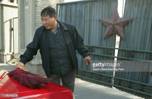 Taxi driver cleans his cab beside the dilapidated gate of a former State Owned Enterprise factory which has been shut down for several years in...