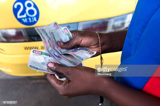 A taxi driver counts a bundle of one hundred Kenyan Schilling bank notes near a local market in Mombasa Kenya on Monday April 29 2013 The number of...