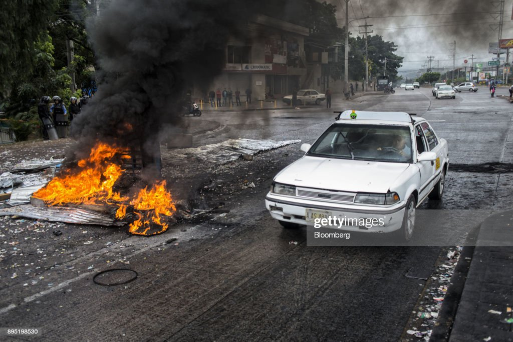 A taxi driver drives past burning tires and debris during protests against the presidential election of Juan Orlando Hernandez in Tegucigalpa, Honduras, on Monday, Dec. 18, 2017. Honduran electoral authorities declared incumbent Hernandez the winner of the Nov. 26 presidential vote after three weeks in which the nation slid into chaos as ballots were counted and recounted. Photographer: Juan Carlos/Bloomberg via Getty Images