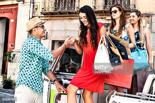Taxi driver giving helping hand to three young women stepping from taxi, Cagliari, Sardinia, Italy