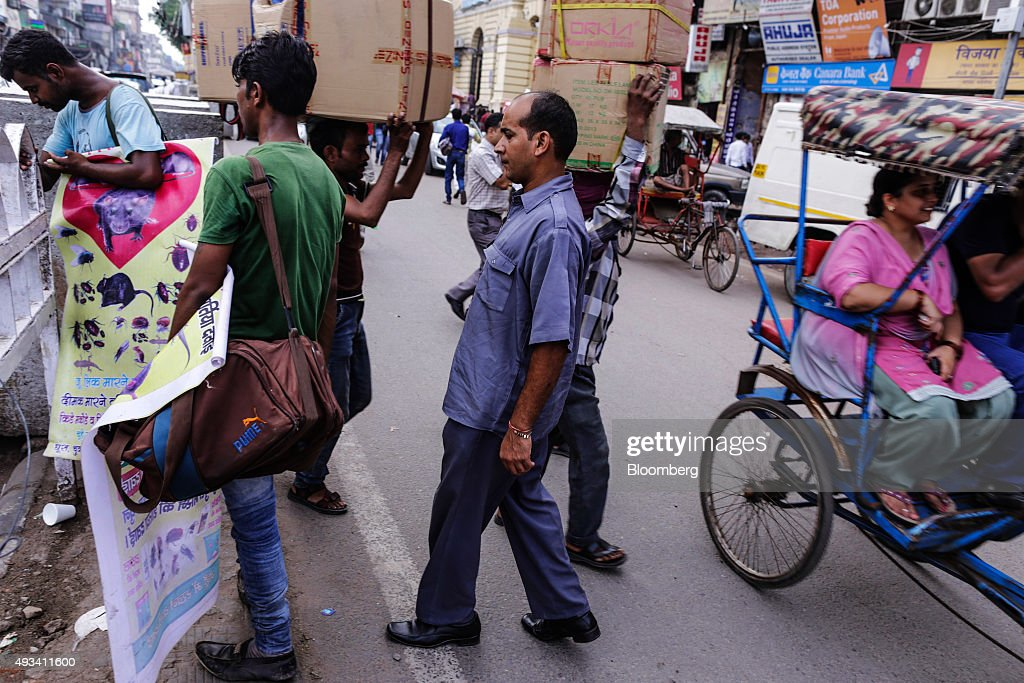 Taxi driver Gurmeet Singh, center, crosses a road in New Delhi, India, on Saturday, Sept. 19, 2015. As cabs lured by app-based platforms proliferate in India, where car ownership is low and public transportation services in most cities and towns havent kept pace with the needs of a growing population, drivers are facing stiffer competition for rides. Photographer: Dhiraj Singh/Bloomberg via Getty Images