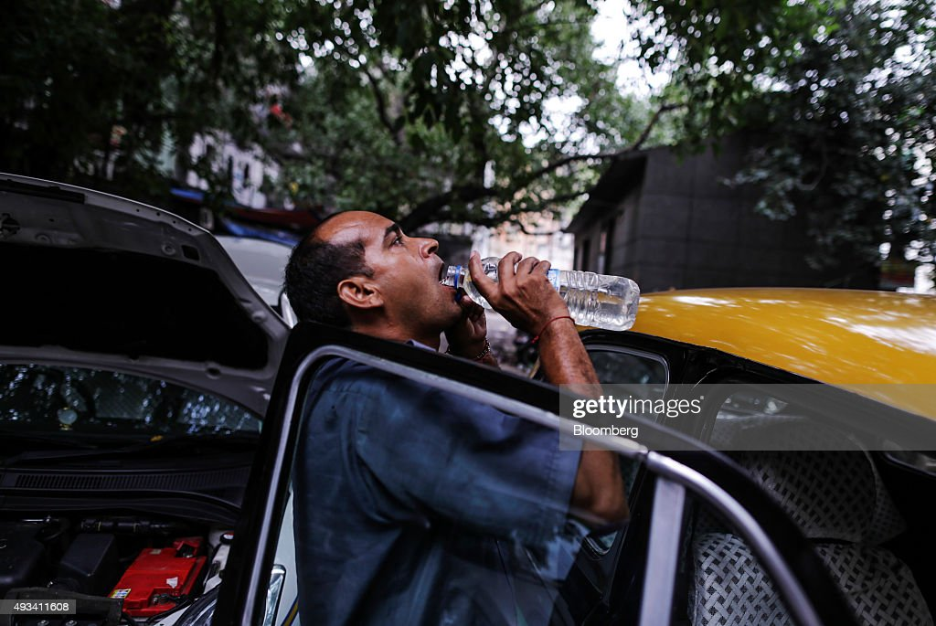 Taxi driver Gurmeet Singh drinks from a bottle of water as he enters a Hindustan Motors Ltd. Ambassador taxi at a taxi stand in New Delhi, India, on Saturday, Sept. 19, 2015. As cabs lured by app-based platforms proliferate in India, where car ownership is low and public transportation services in most cities and towns havent kept pace with the needs of a growing population, drivers are facing stiffer competition for rides. Photographer: Dhiraj Singh/Bloomberg via Getty Images