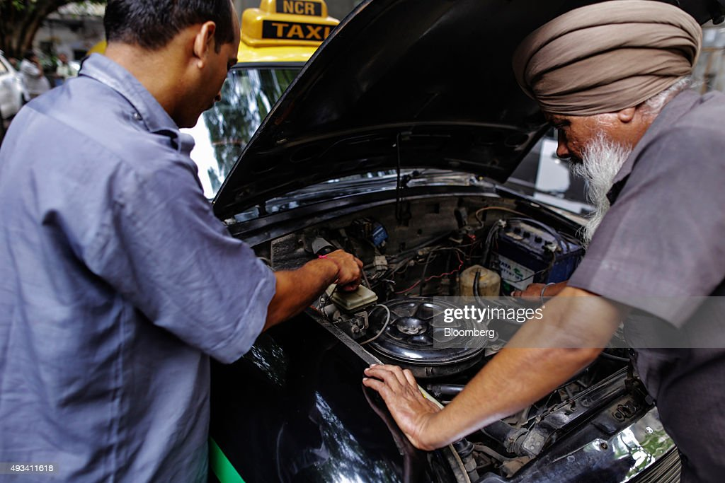 Taxi driver Gurmeet Singh, left, works on the engine of a Hindustan Motors Ltd. Ambassador taxi at a taxi stand in New Delhi, India, on Saturday, Sept. 19, 2015. As cabs lured by app-based platforms proliferate in India, where car ownership is low and public transportation services in most cities and towns havent kept pace with the needs of a growing population, drivers are facing stiffer competition for rides. Photographer: Dhiraj Singh/Bloomberg via Getty Images