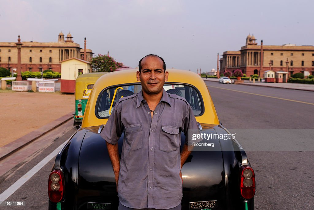 Taxi driver Gurmeet Singh poses for a photograph in front of a Hindustan Motors Ltd. Ambassador taxi on King's Way boulevard in New Delhi, India, on Saturday, Sept. 19, 2015. As cabs lured by app-based platforms proliferate in India, where car ownership is low and public transportation services in most cities and towns havent kept pace with the needs of a growing population, drivers are facing stiffer competition for rides. Photographer: Dhiraj Singh/Bloomberg via Getty Images