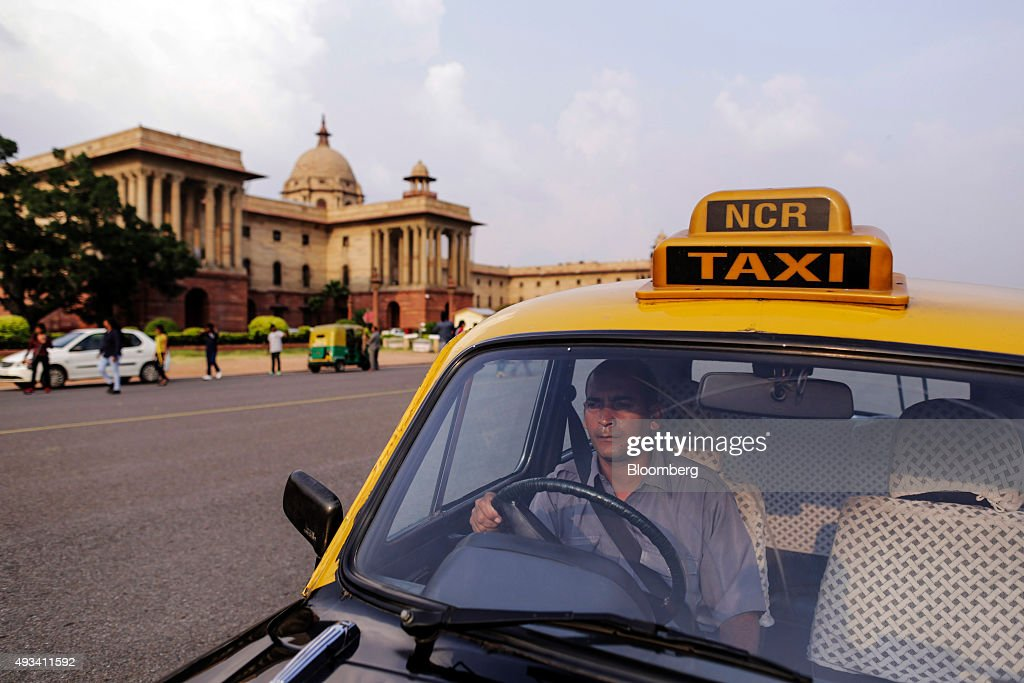 Taxi driver Gurmeet Singh sits inside a Hindustan Motors Ltd. Ambassador taxi at a taxi stand on King's Way boulevard in New Delhi, India, on Saturday, Sept. 19, 2015. As cabs lured by app-based platforms proliferate in India, where car ownership is low and public transportation services in most cities and towns havent kept pace with the needs of a growing population, drivers are facing stiffer competition for rides. Photographer: Dhiraj Singh/Bloomberg via Getty Images