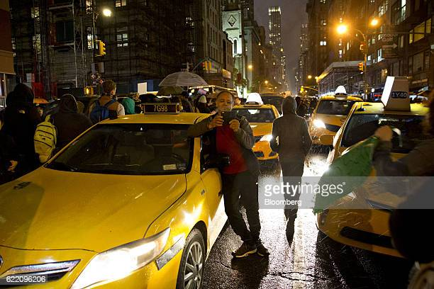 A taxi driver holds a mobile device while he stands beside his vehicle as demonstrators march from Union Square to Trump Tower during a protest...