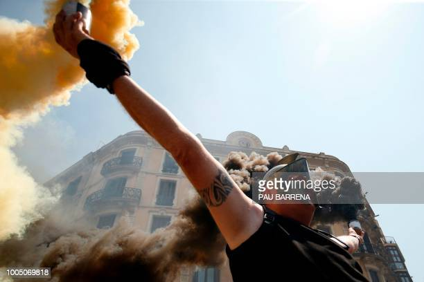 Taxi driver holds flares as protesters gather outside the government delegation office during a strike by cab drivers in Barcelona on July 25, 2018.