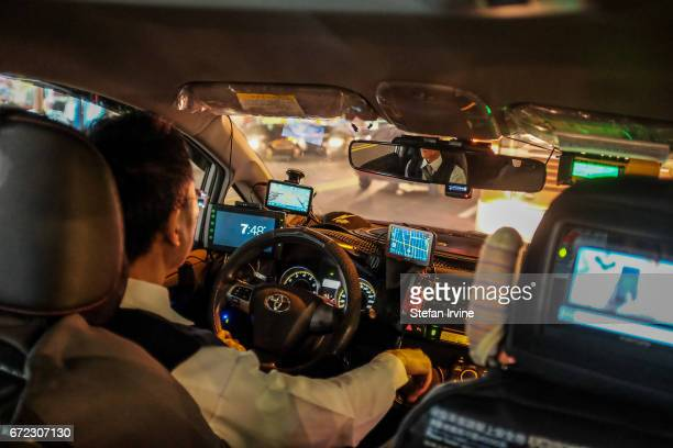 A taxi driver in nighttime Taipei with an array of technology devices installed on his car's dashboard