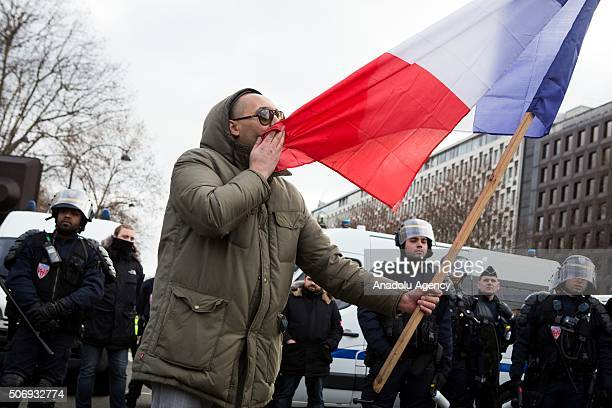 A taxi driver is kissing the French flag in front of Riot Police during a protest in Porte Maillot against competition from Uber in Paris on January...