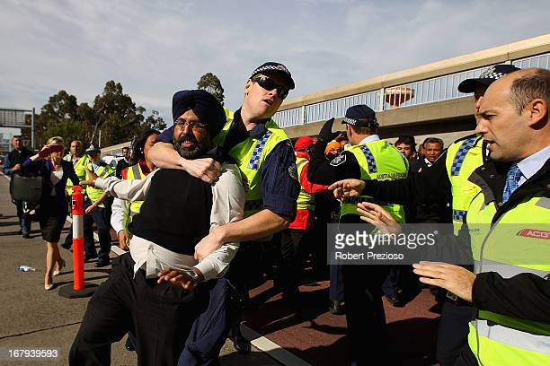 A taxi driver is tackled by a police officer during a protest at Melbourne Airport on May 3 2013 in Melbourne Australia Taxi drivers in Melbourne are...