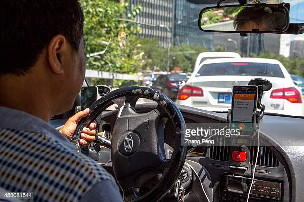 A taxi driver is using Didi Dacha App while driving on the way China Investment Corporation has made an undisclosed investment in Chinese taxihailing...