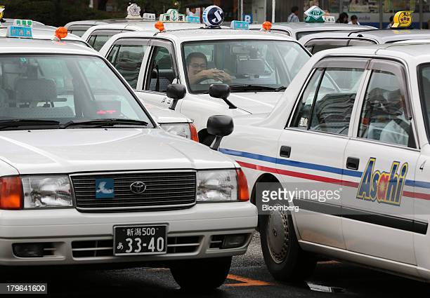 A taxi driver leans forward on his steering wheel as rows of taxis wait for customers outside a train station in Niigata Japan on Thursday Sept 5...