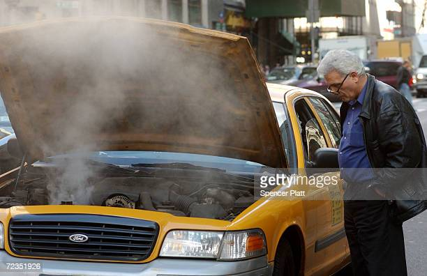 A taxi driver looks at his overheating engine February 22 2002 in New York City Claiming that the taxi industry can not attract enough drivers New...